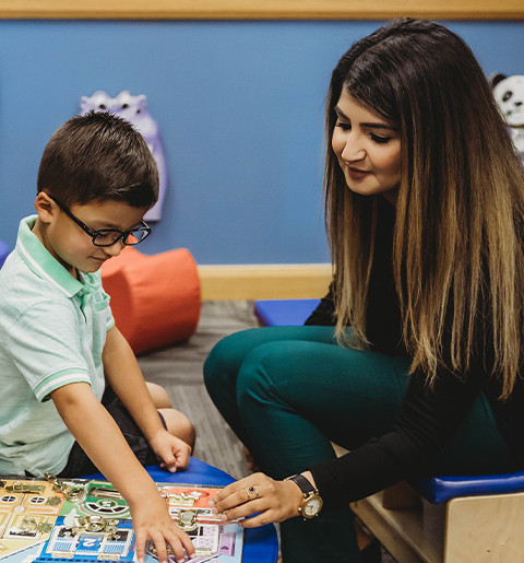 Dr. Fiza Khan, board-certified child psychiatrist, talks to a young boy patient.
