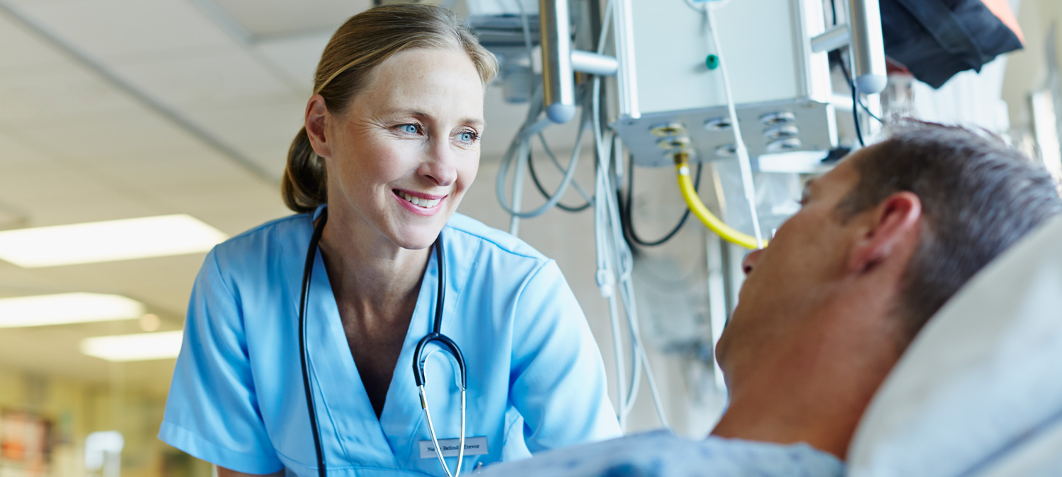 Smiling female provider with stethoscope around her neck observes man resting in hospital bed.