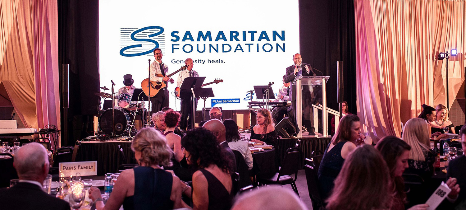 Band and announcer onstage at Samaritan Foundation gala with people in formalwear seated at tables in foreground.