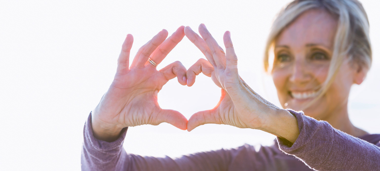 Close-up of woman holding hands up to form heart.