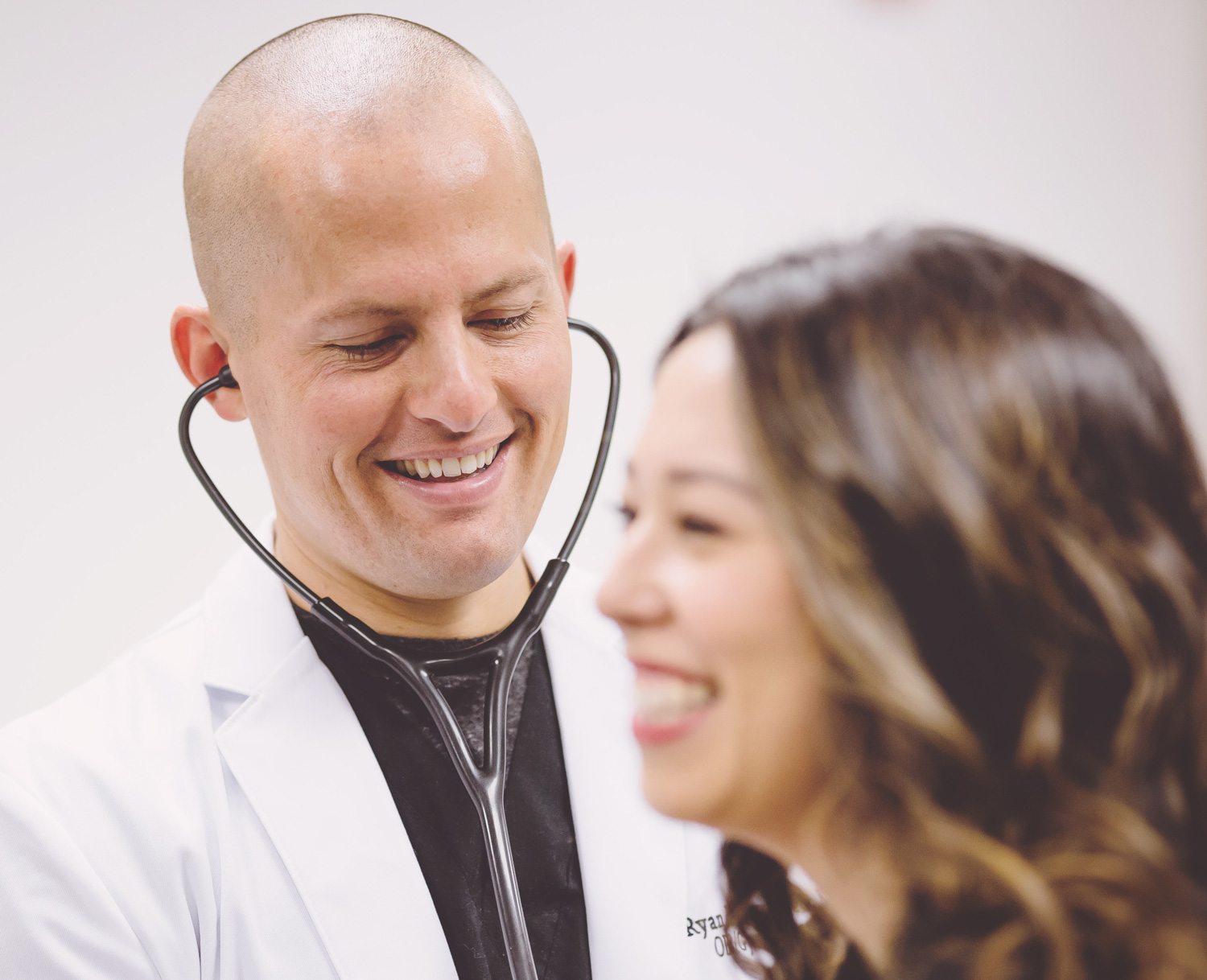 Dr. Ryan Rasmussen, OB/GYN, listens to woman's heart with stethoscope.