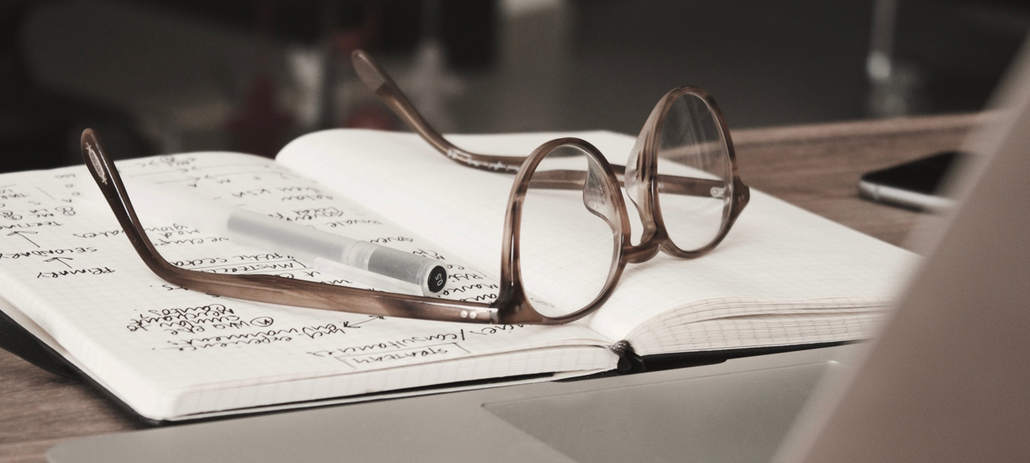 Eyeglasses and pen on an open notebook