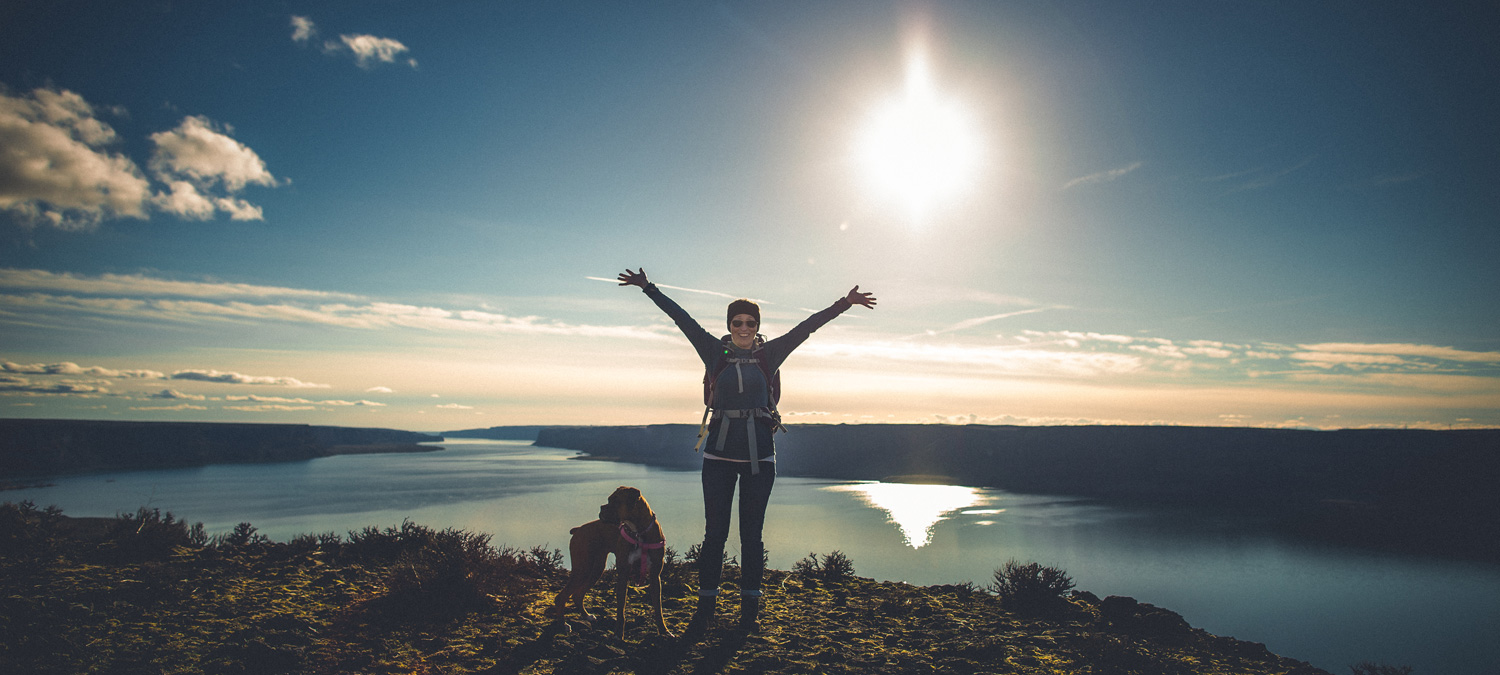 Woman hiker raises her arms on top of a hill with sunset behind her over a lake and dog at her feet.