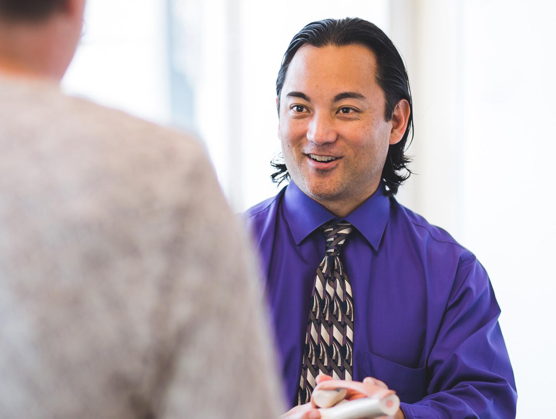 Dr. Leo Chough talks to patient.