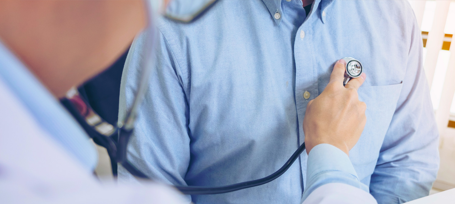 Close-up of provider holding stethoscope to man's chest. Both wear pale blue shirts. No faces visible.