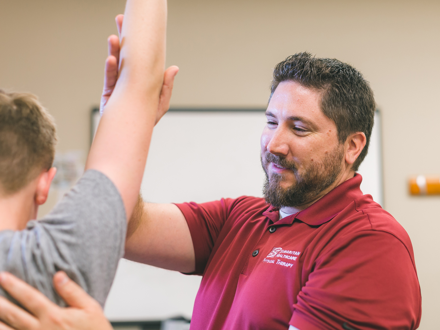 Physical therapist helps young man stretch arm.
