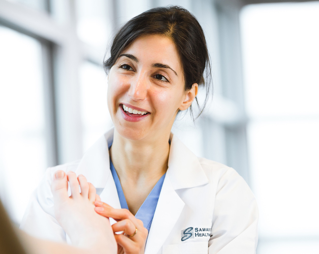 Smiling Dr. Arezou Amidi, examines patient's foot.