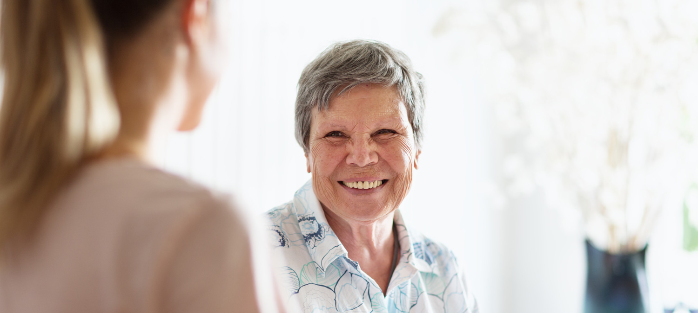 Smiling older female volunteer greets woman